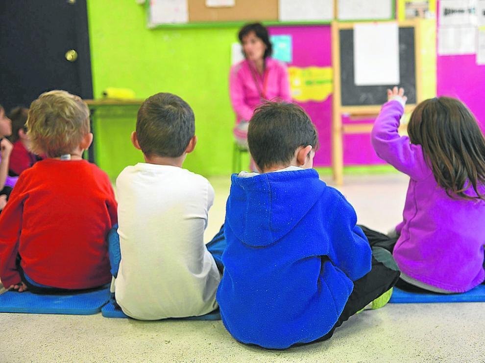 Niños pequeños atienden las explicaciones de la maestra en un colegio de Zaragoza.