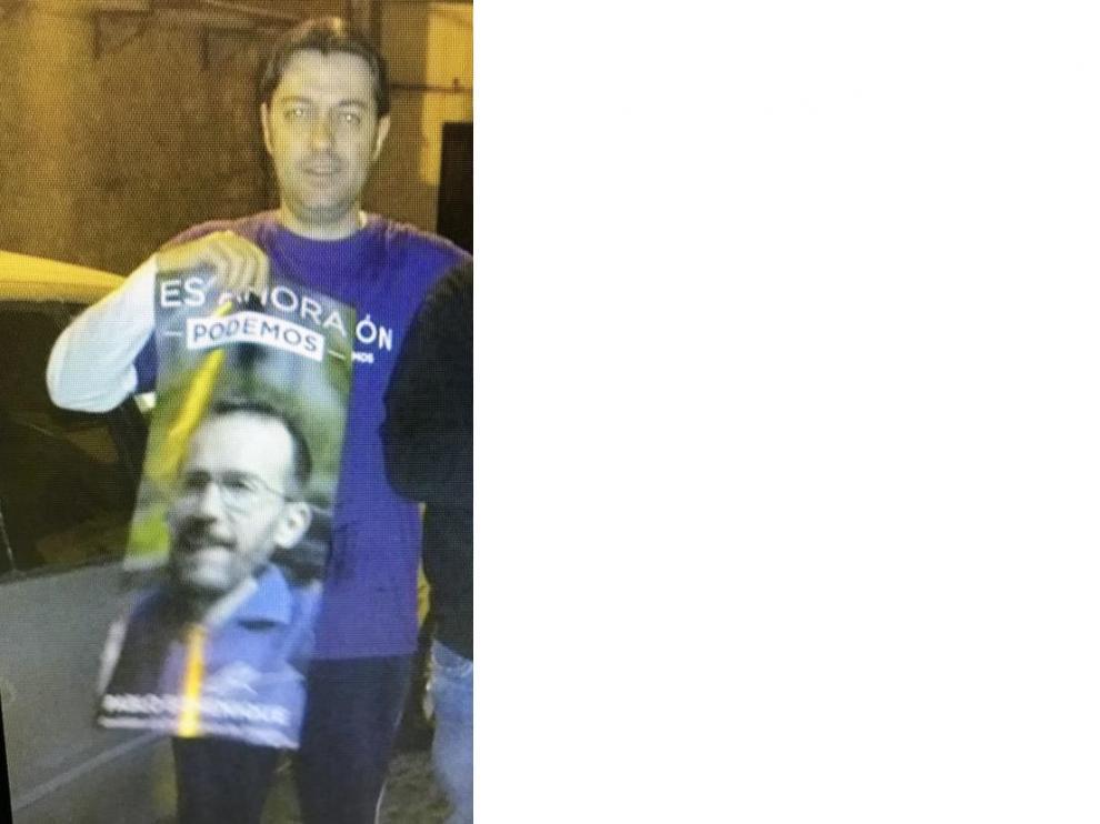 El candidato de Vox en Tarazona, Javier Moya, pegando un cartel electoral de Podemos