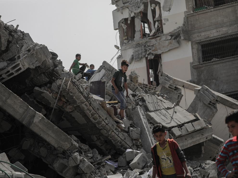 Varios niños jugando entre las ruinas de un edificio en Gaza