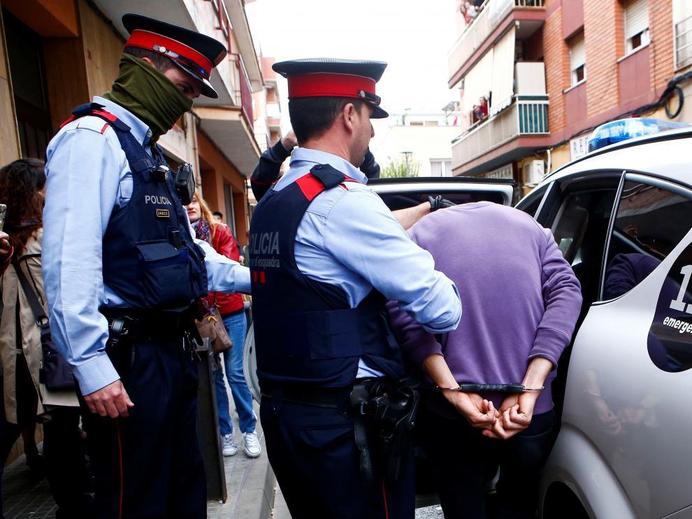 Uno de los detenidos escoltado por los mossos