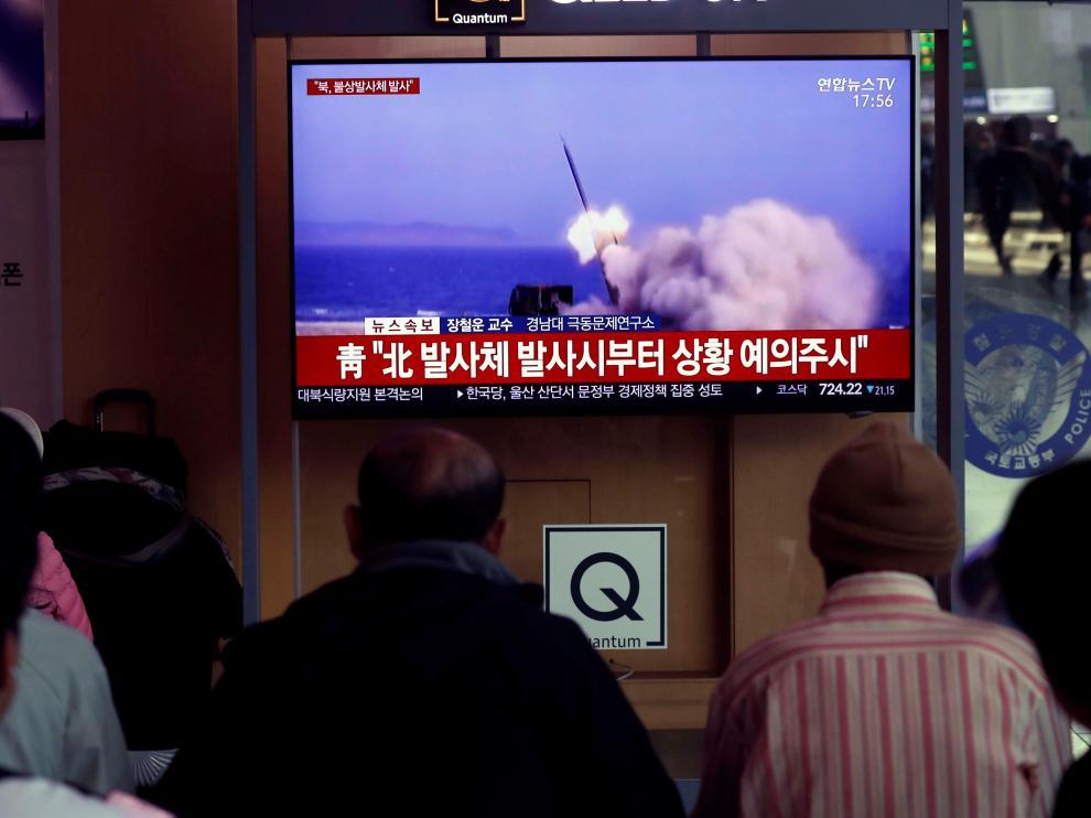 Varios surcoreanos siguen por televisión el lanzamiento de una serie de proyectiles.