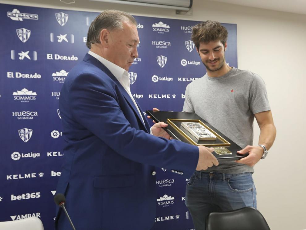 El presidente de la SD Huesca , Agustín Lasaosa, le entrega una placa conmemorativa a Gonzalo Melero.