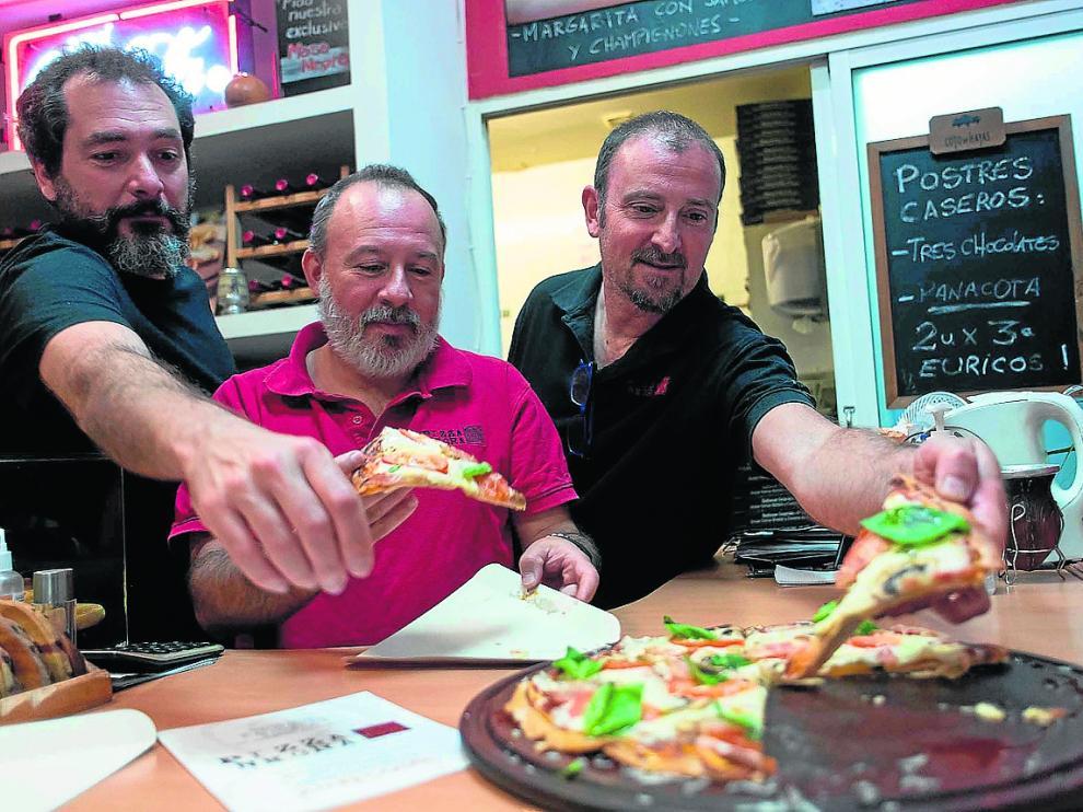 Hernán Romero, Javier Harguindeguy y Pablo Lozano cogiendo una pizza negra.