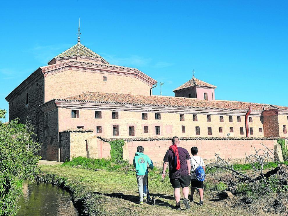 Tres niños contemplan el antiguo convento de Gea de Albarracín, ahora convertido en residencia.