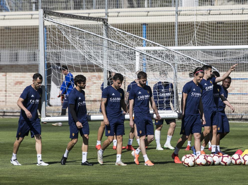 Los jugadores del Zaragoza trasladan una portería en el entrenamiento de ayer.