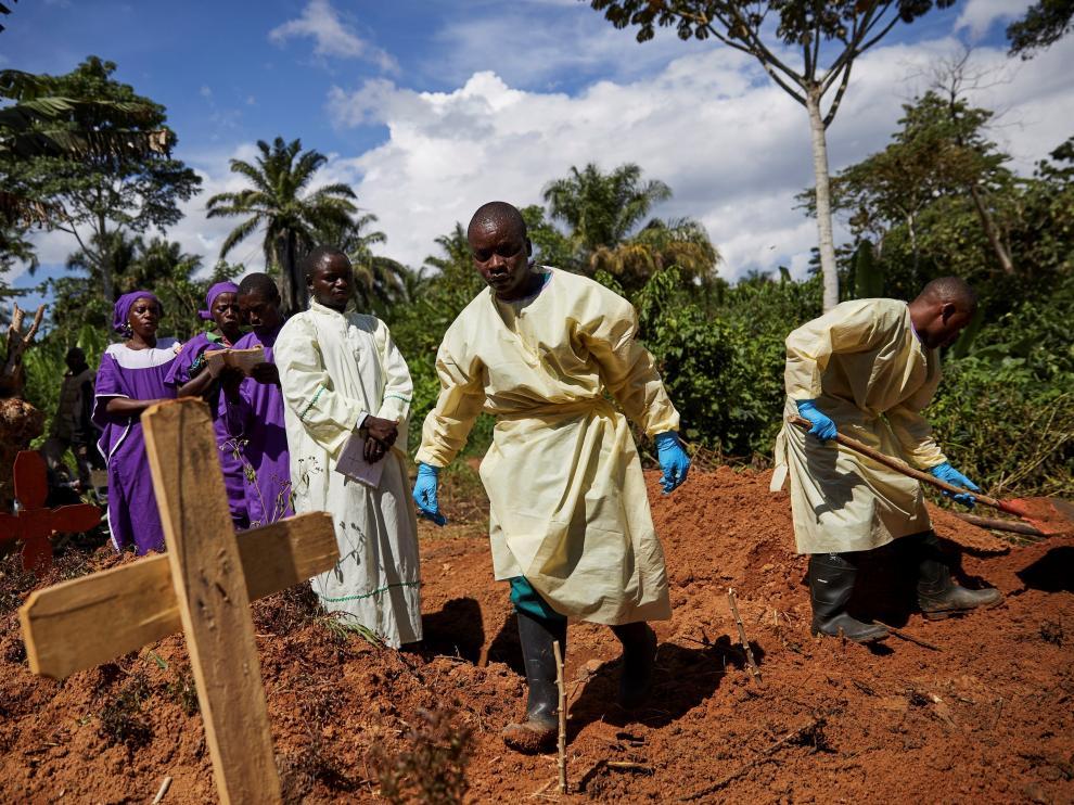 Varios trabajadores sanitarios entierran el cadáver de un hombre que se infectó con ébola tras compartir habitación de hospital con un paciente enfermo en Beni (República Democrática del Congo).