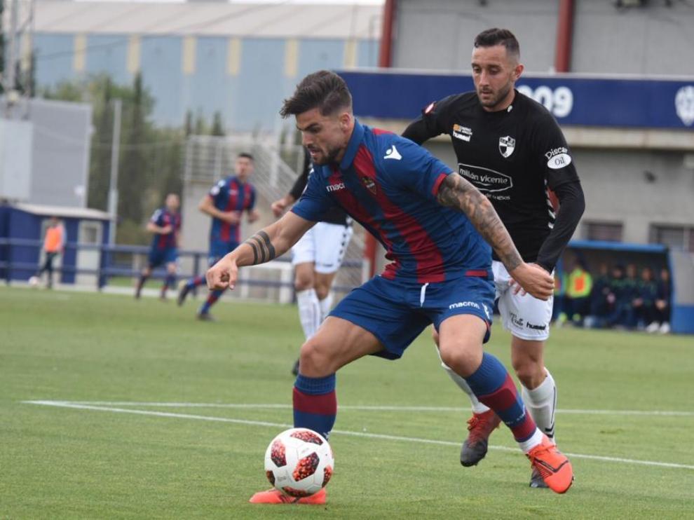 Un jugador del Levante B defiende ante la presión de un rival del CD Ebro.