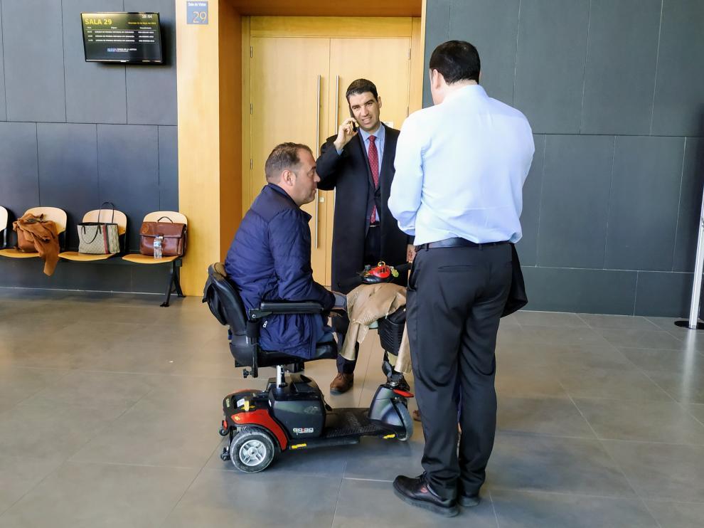 El demantante, en silla de ruedas, junto a su abogado, Víctor Laguardia, hablando por teléfono.