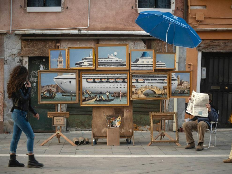 """A street stall with oil paintings creating an image of a yacht in the Venice canal with a sign reading """"Venice in oil"""", set up by a person purporting to be British artist Banksy, in Venice, Italy, May 22, 2019, in this image obtained from Banksy's social media. Courtesy of Instagram @banksy/Social Media via REUTERS. ATTENTION EDITORS - THIS IMAGE HAS BEEN SUPPLIED BY A THIRD PARTY. MANDATORY CREDIT INSTAGRAM @BANKSY. NO RESALES. NO ARCHIVES. [[[REUTERS VOCENTO]]] ART-BANKSY/VENICE-UGC"""