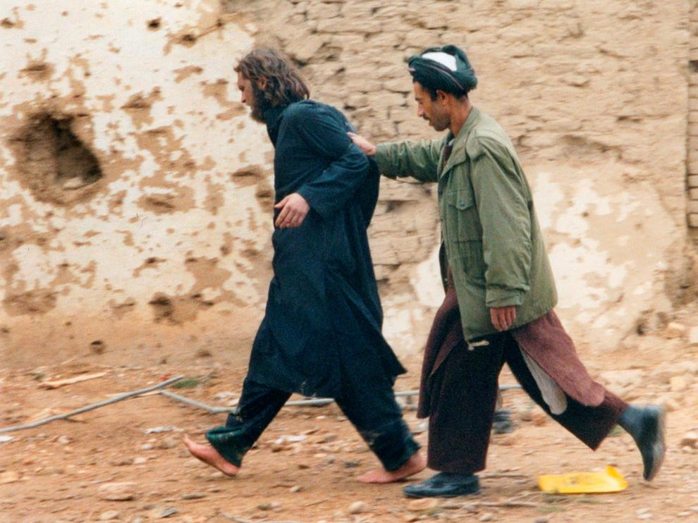 FILE PHOTO: U.S.-born John Walker Lindh (L) is led away by a Northern Alliance soldier after he was captured among al Qaeda and Taliban prisoners following an uprising at the Fort Qali-i-Janghi prison near Mazar-i-Sharif December 1, 2001 REUTERS/STR/File Photo [[[REUTERS VOCENTO]]] USA-CRIME/LINDH