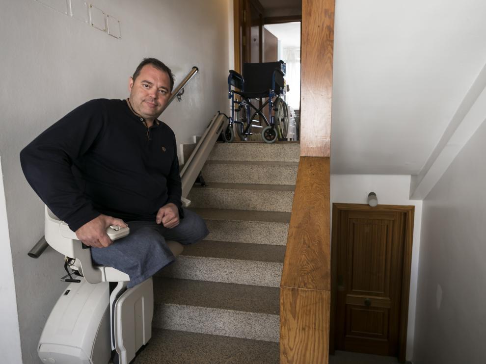 Eugenio Rodríguez, en la silla elevadora instalada en las escaleras que dan acceso a su vivienda en Zaragoza.