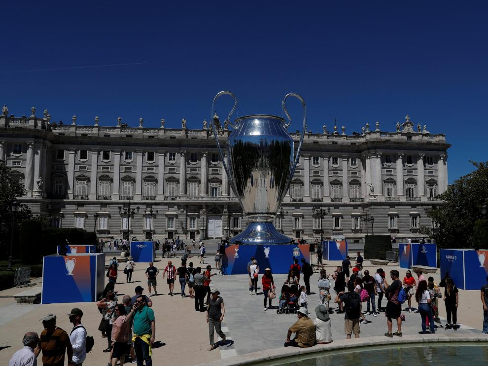 People hang out next to a giant replica of the UEFA Champions League trophy that is displayed outside the Royal Palace in Madrid, Spain, May 30, 2019. REUTERS/Susana Vera [[[REUTERS VOCENTO]]] CHAMPIONS-TOT-LIV/PREVIEW