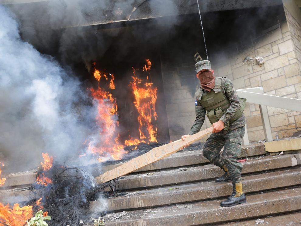Un soldado intenta apagar los neumáticos en llamas en una de las puertas de acceso a la Embajada de Estados Unidos.
