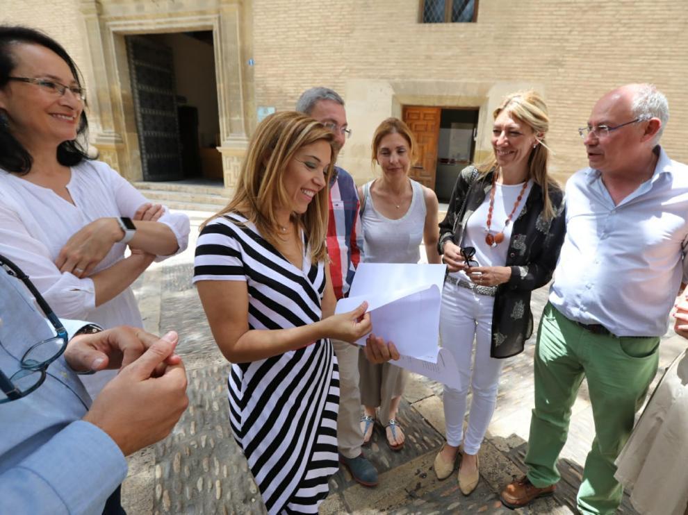 Ana Alós, delante del Ayuntamiento y acompañada por sus concejales, hojea el documento con la proposición de la moción de censura que  solo han firmado los nueves ediles populares