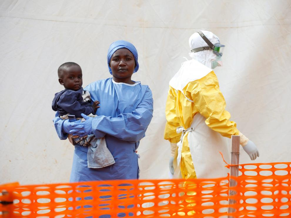 FILE PHOTO: Mwamini Kahindo, an Ebola survivor working as a caregiver to babies who are confirmed Ebola cases, holds an infant outside the red zone at the Ebola treatment centre in Butembo, Democratic Republic of Congo, March 25, 2019. REUTERS/Baz Ratner/File Photo [[[REUTERS VOCENTO]]] HEALTH-EBOLA/SOCIETY