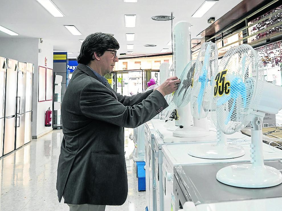 Un cliente mira un ventilador en una tienda de Zaragoza para adquirirlo en plena ola de calor.