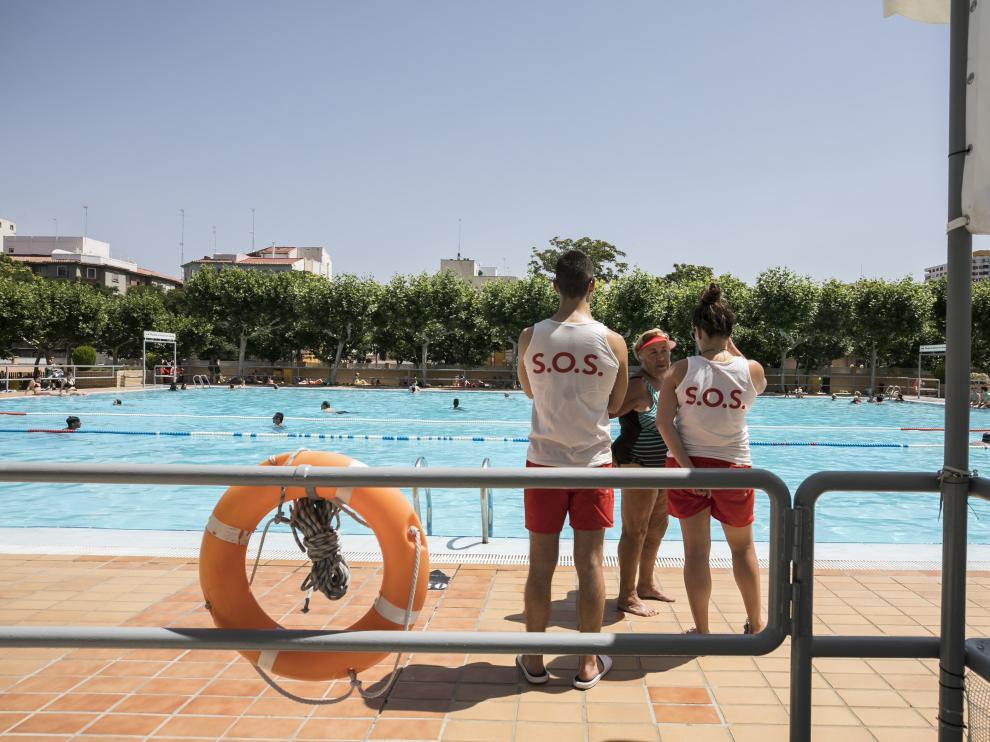 Una bañista conservaba este viernes con dos de los socorristas de las piscinas de Ciudad Jardín de Zaragoza.
