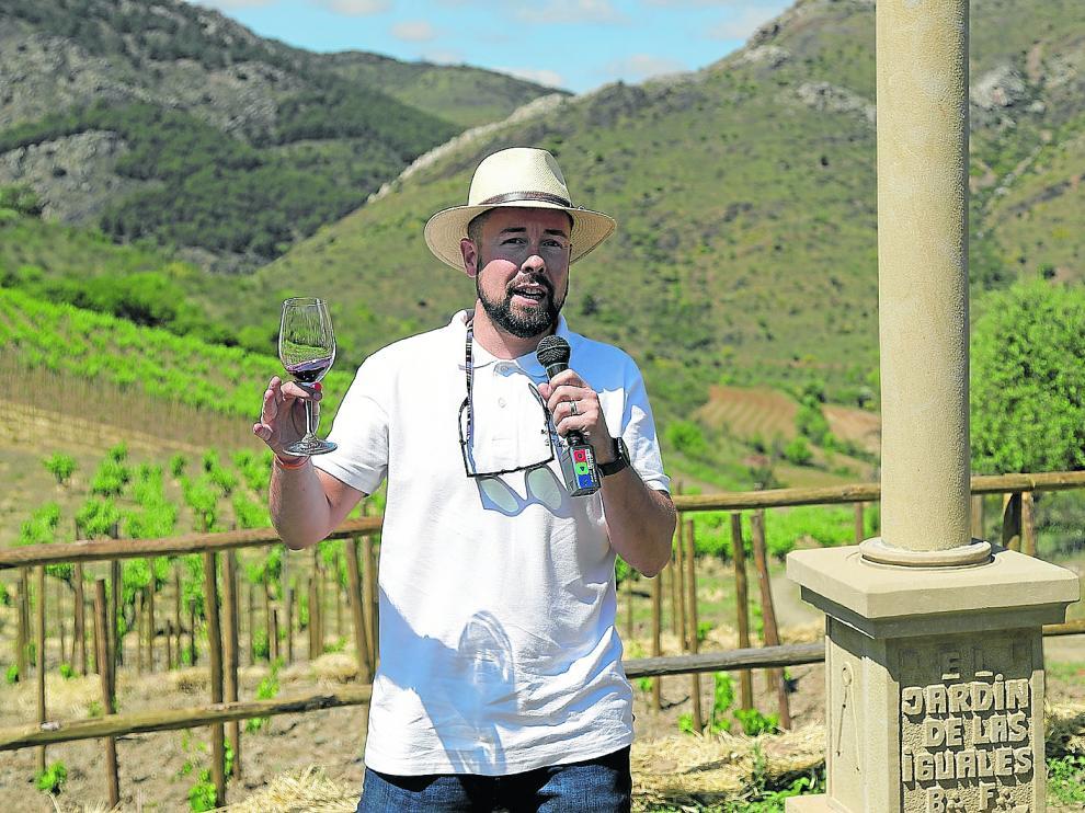 Fernando Mora, con una copa junto al peirón instalado en la finca que da nombre al vino, El Jardín de las Iguales.