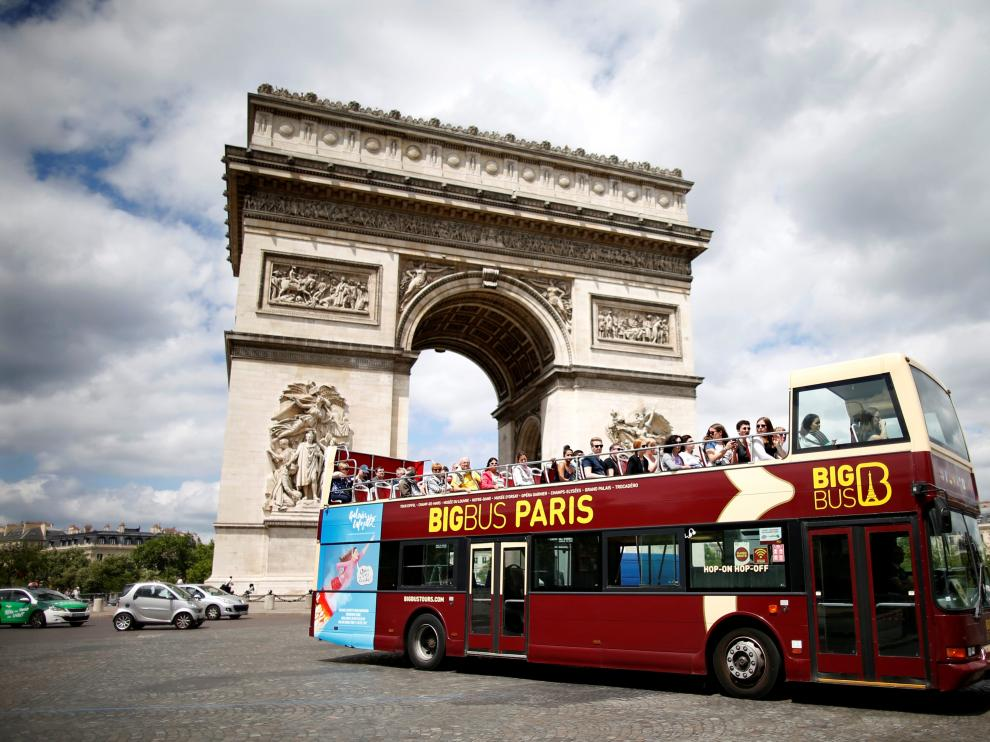 FILE PHOTO: Tourists ride in an open-air double-decker bus past the Arc de Triomphe in Paris, France, May 30, 2017. REUTERS/Charles Platiau/File Photo [[[REUTERS VOCENTO]]] FRANCE-TOURISM/
