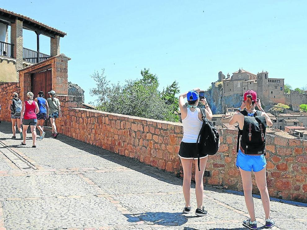 Dos turistas hacen fotos, este sábado, al castillo colegiata de Alquézar.