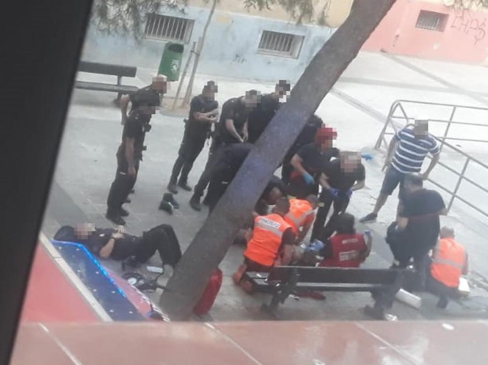 Los sanitarios tratan de reanimar al hombre. A la izquierda, uno de los policías agredidos, tumbado en el suelo.