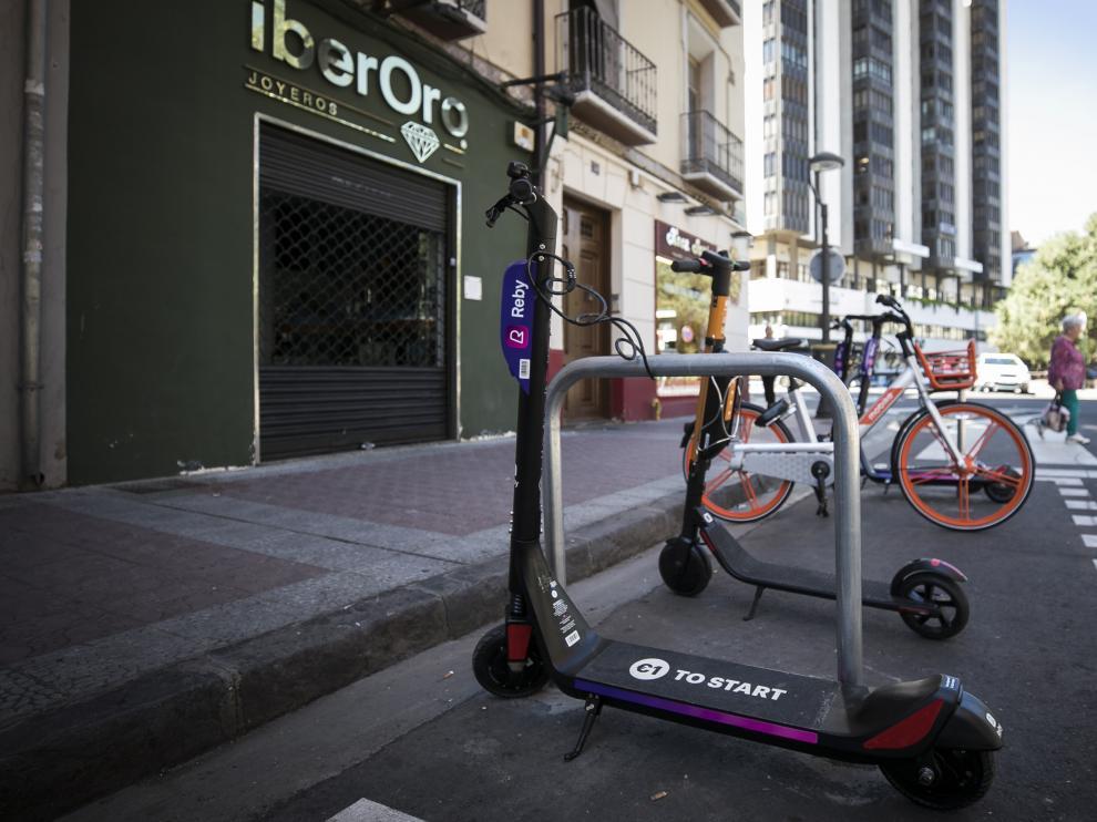 Una bicicleta de Mobike y patinetes, en uno de los aparcamientos habilitados por el Ayuntamiento de Zaragoza.