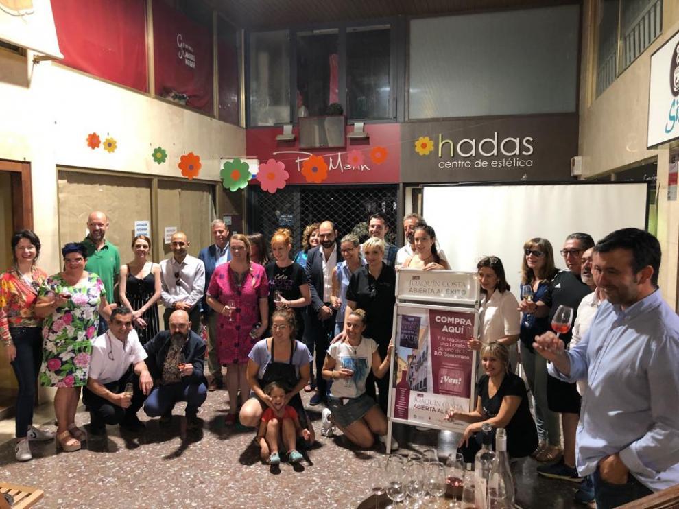 Miembros de la corporación municipal, del comercio y del sector del vino con comercios de la calle.