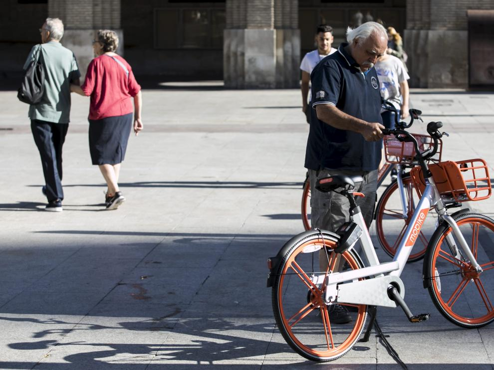 Un usuario de las bicicletas de Mobike, en la plaza del Pilar de Zaragoza.