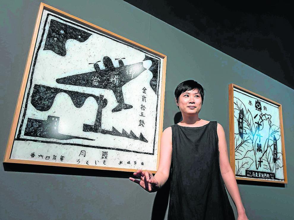 La artista Hoy I-Ting posa delante de varias piezas de la exposición 'Tejiendo identidades'.