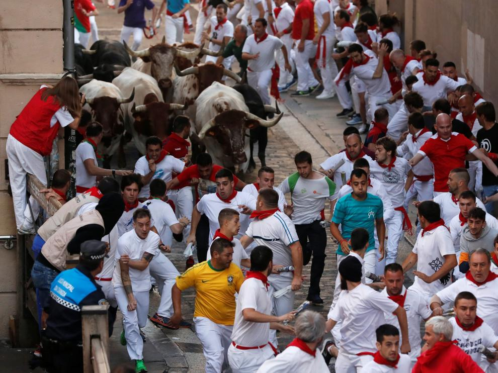 A reveller lays on the ground near bulls and steers during the running of the bulls at the San Fermin festival in Pamplona, Spain, July 11, 2019. REUTERS/Jon Nazca [[[REUTERS VOCENTO]]] SPAIN-CULTURE/BULLS