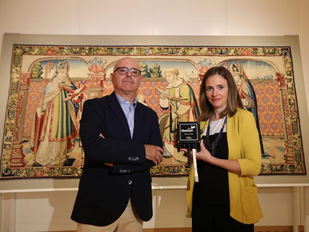 Fernando Sarriá y Alicia Asín muestran el sensor delante del tapiz de Roda de Isábena.