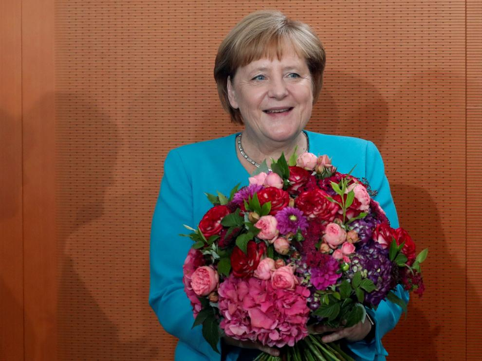Chancellor Angela Merkel reacts after receiving a bouquet of flowers for her 65th birthday at the cabinet meeting in Berlin, Germany, July 17, 2019. REUTERS/Fabrizio Bensch [[[REUTERS VOCENTO]]] GERMANY-POLITICS/