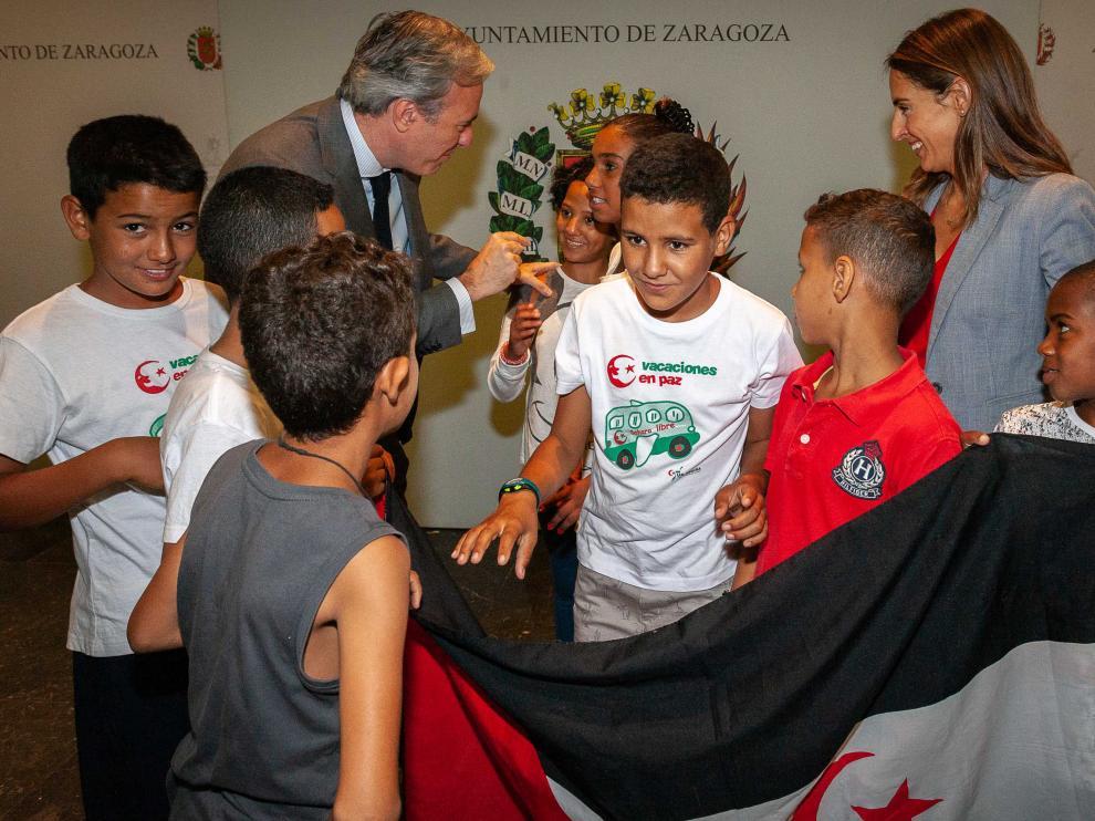 El alcalde de Zaragoza, Jorge Azcón, charla con varios de los niños llegados a la capital