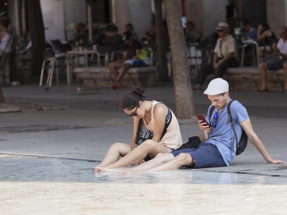 Dos personas se refrescan, ayer en la fuente de Goya de la plaza del Pilar de la capital