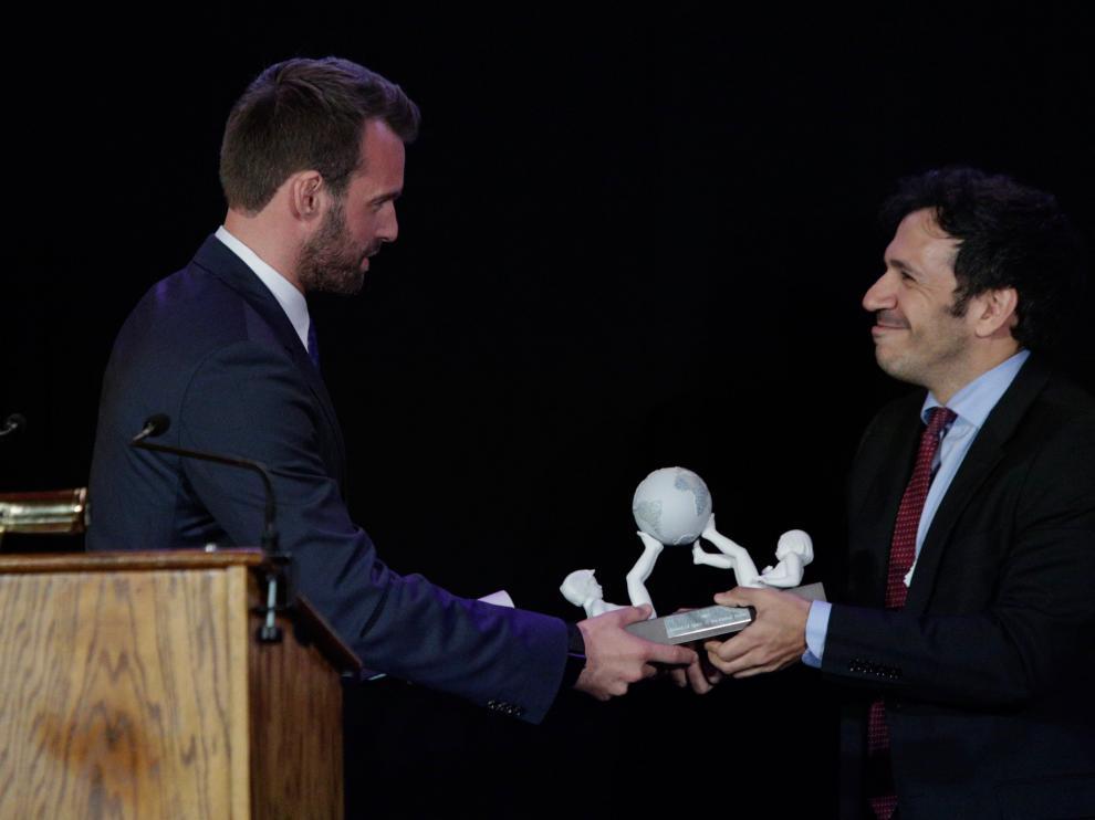 El representante de HBO, David Coupland, recibe un galardón de parte de José Antonio Gil, durante la entrega de premios de 'Amigos de España'.