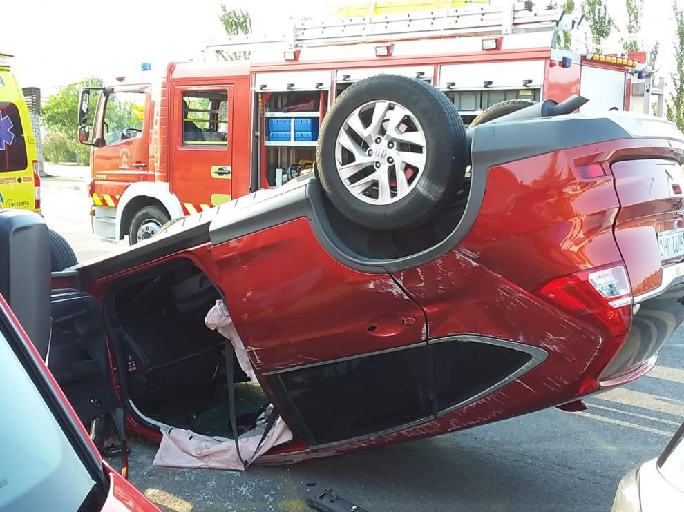 Un vehículo volcado en la avenida de la Ciudad de Soria, donde se ha producido el accidente.