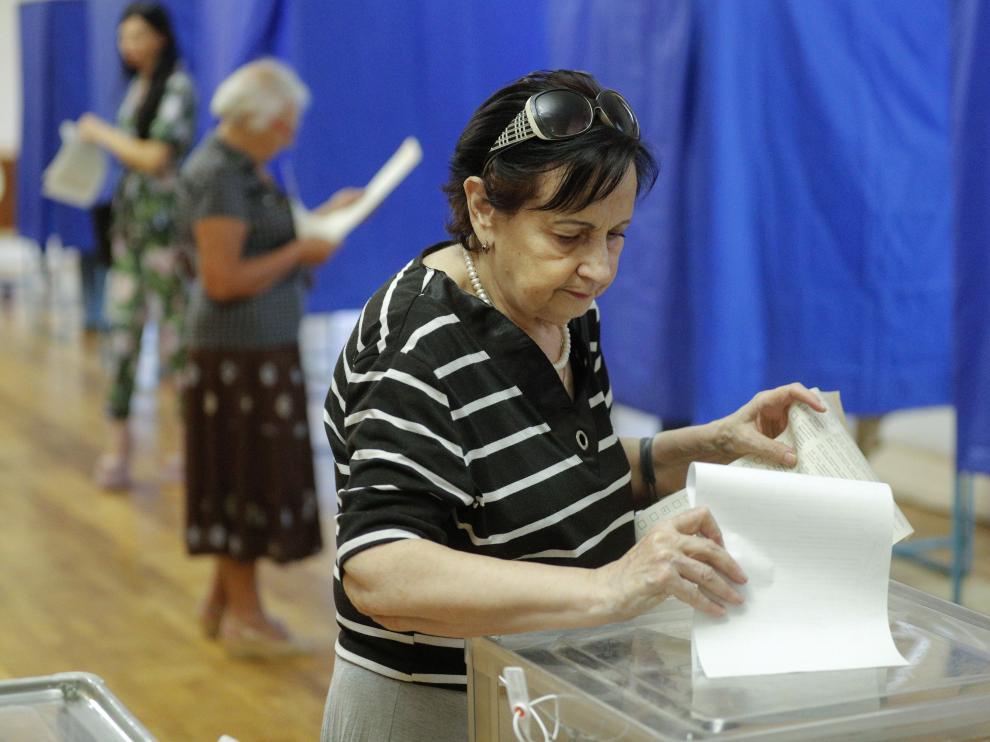 Una mujer deposita su voto en las elecciones al parlamento de Ucrania.