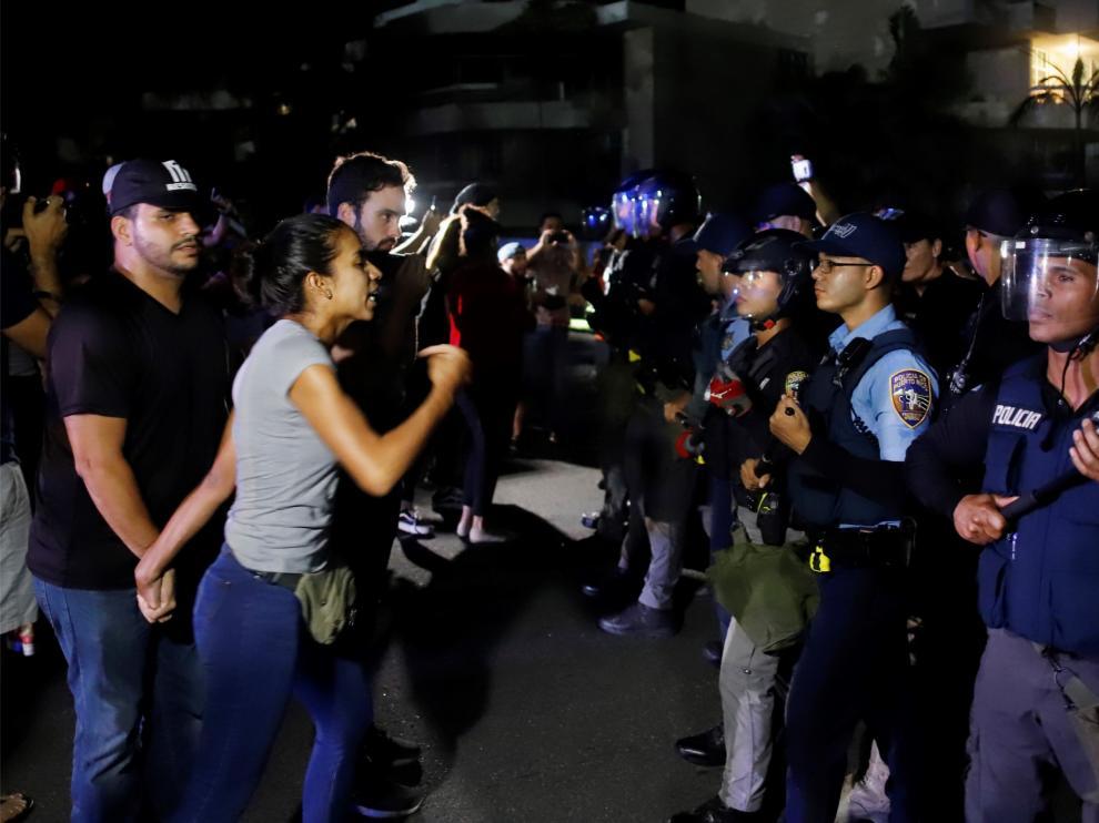 Manifestantes se enfrentan a la policía mientras el gobernador Ricardo Roselló mantiene una reunión con alcaldes federados.