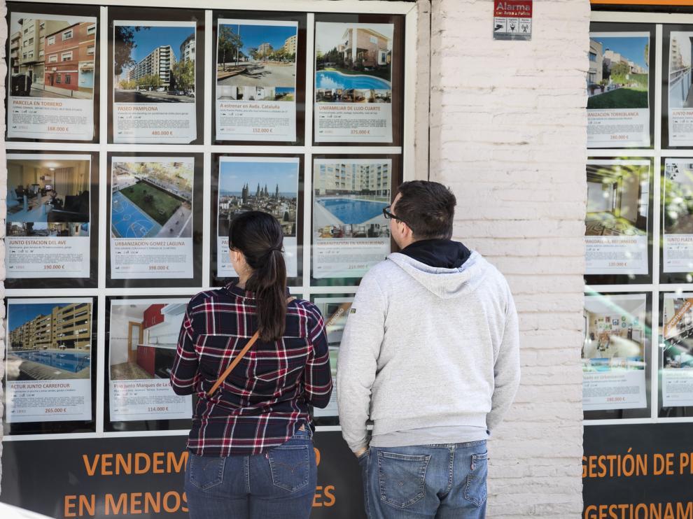 Una pareja mira anuncios de pisos en una inmobiliaria.