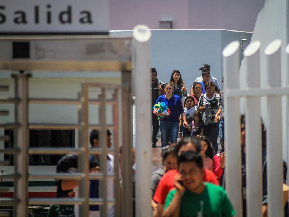 Decenas de inmigrantes retornan este martes a México por la garita del chaparral, en la ciudad de Tijuana.