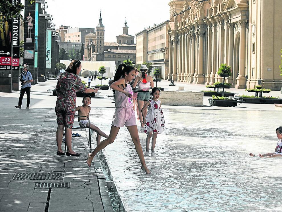 Varias personas se refrescan para combatir el calor, este martes en la fuente de Goya de Zaragoza.