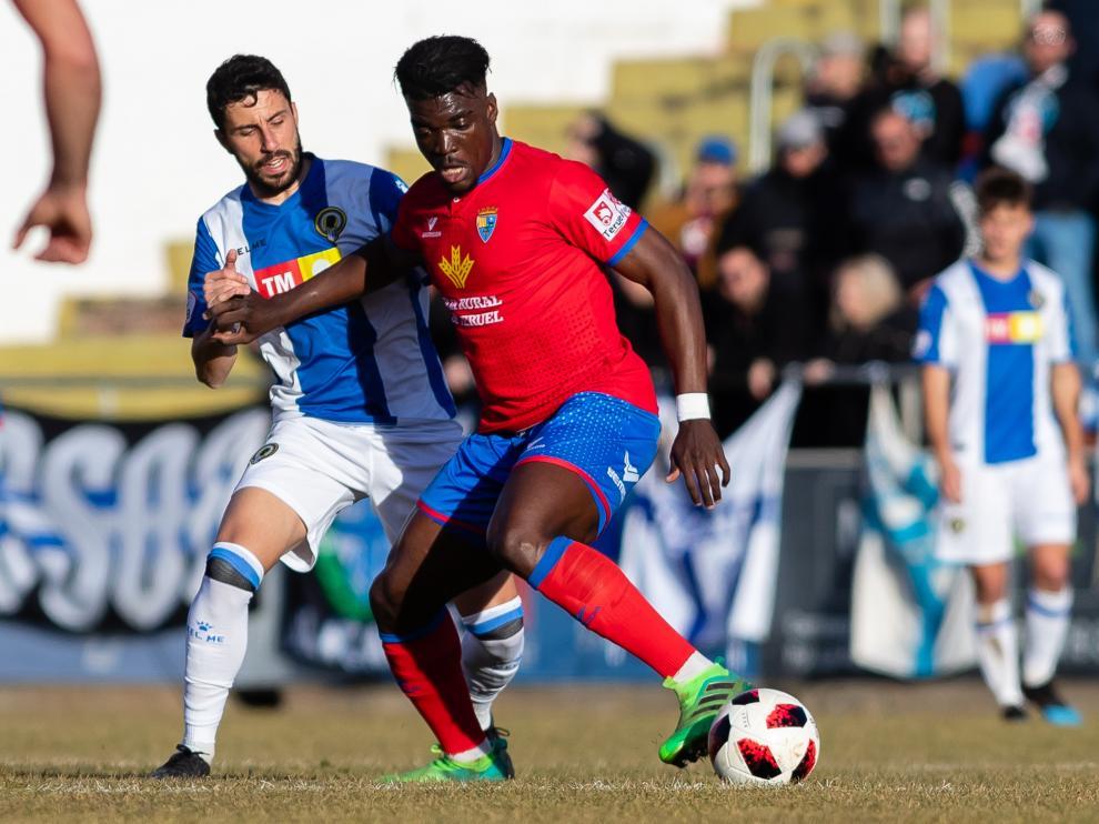 Un jugador del CD Teruel protege el balón ante la presión de un futbolista del Hércules.