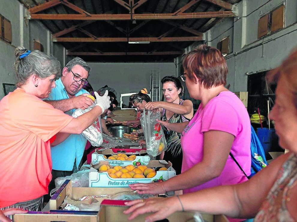 Varios vecinos preparan bolsas con comida y bebida para el operativo de extinción.