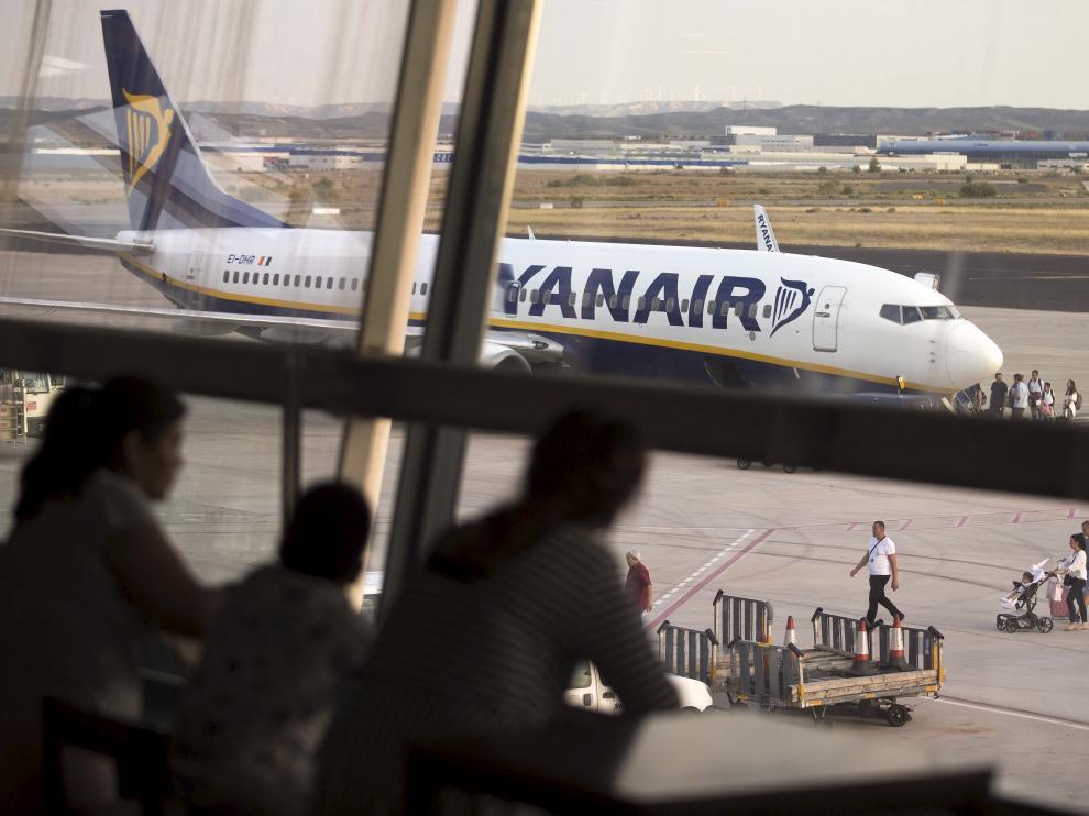 Un grupo de pasajeros observan un avión de Ryanair desde los ventanales del aeropuerto de Zaragoza.