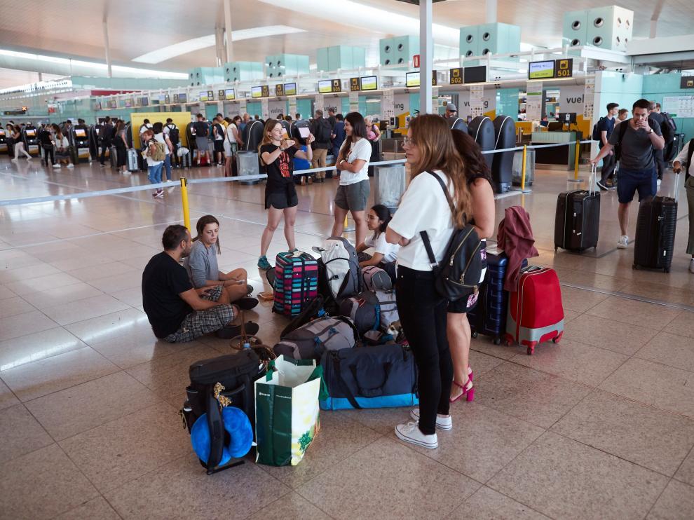 arias personas esperan este sábado frente los mostradores de la aerolínea Vueling