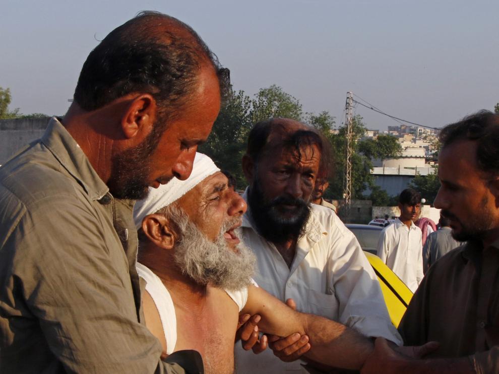 Varias personas ayudan a trasladar a un herido en el accidente áereo ocurrido en una zona de viviendas de Rawalpindi (Pakistán).