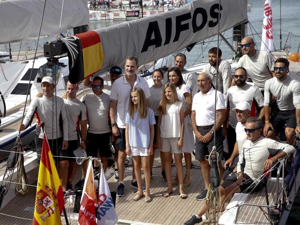 Los reyes y sus hijas posan junto a la tripulación de AIPOS.