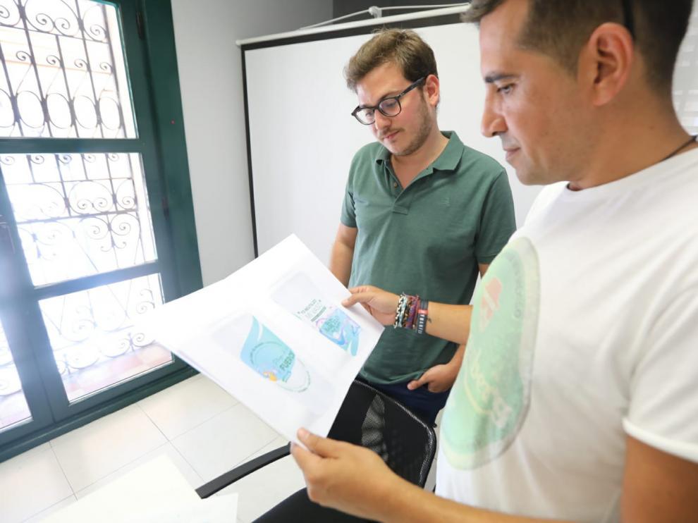 Carlos Bordonaba, del bar El Palmar, y Adrián Bailo, del Tararí, muestran los diseños que tendrán los vasos y copas reutilizables.