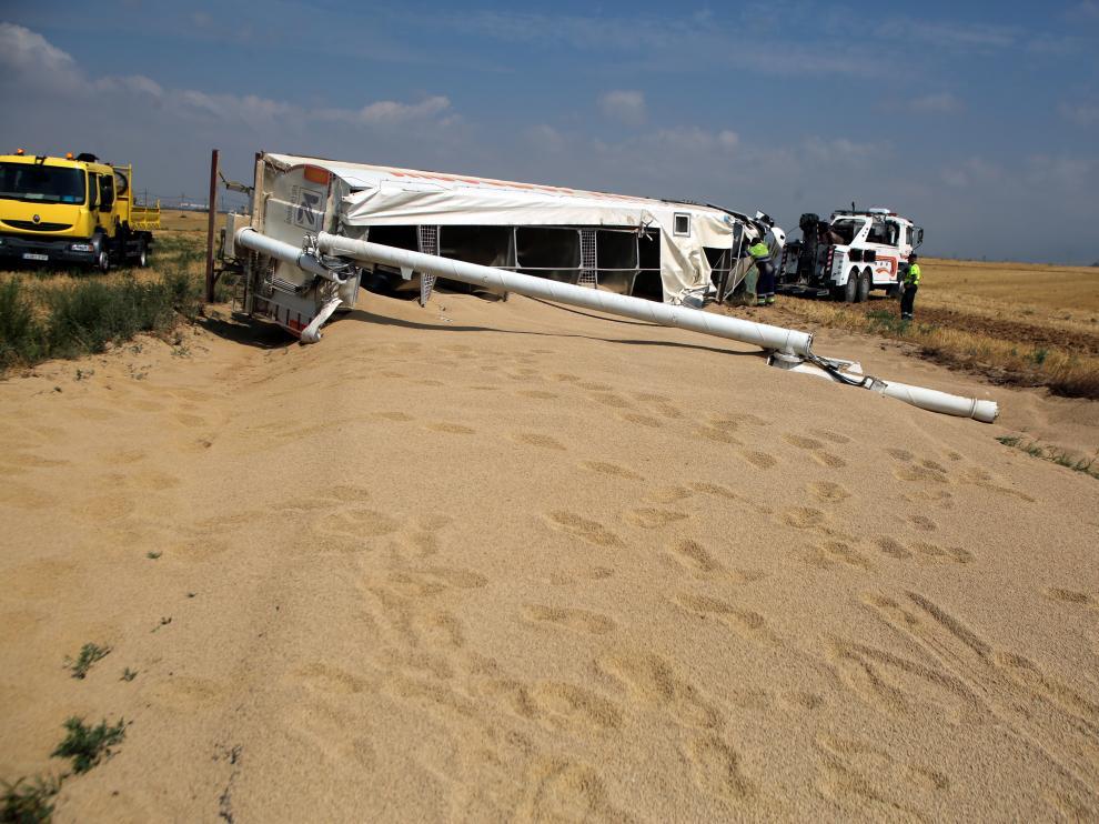 El camión ha volcando ocupando toda la calzada y ha perdido la carga de grano que transportaba.