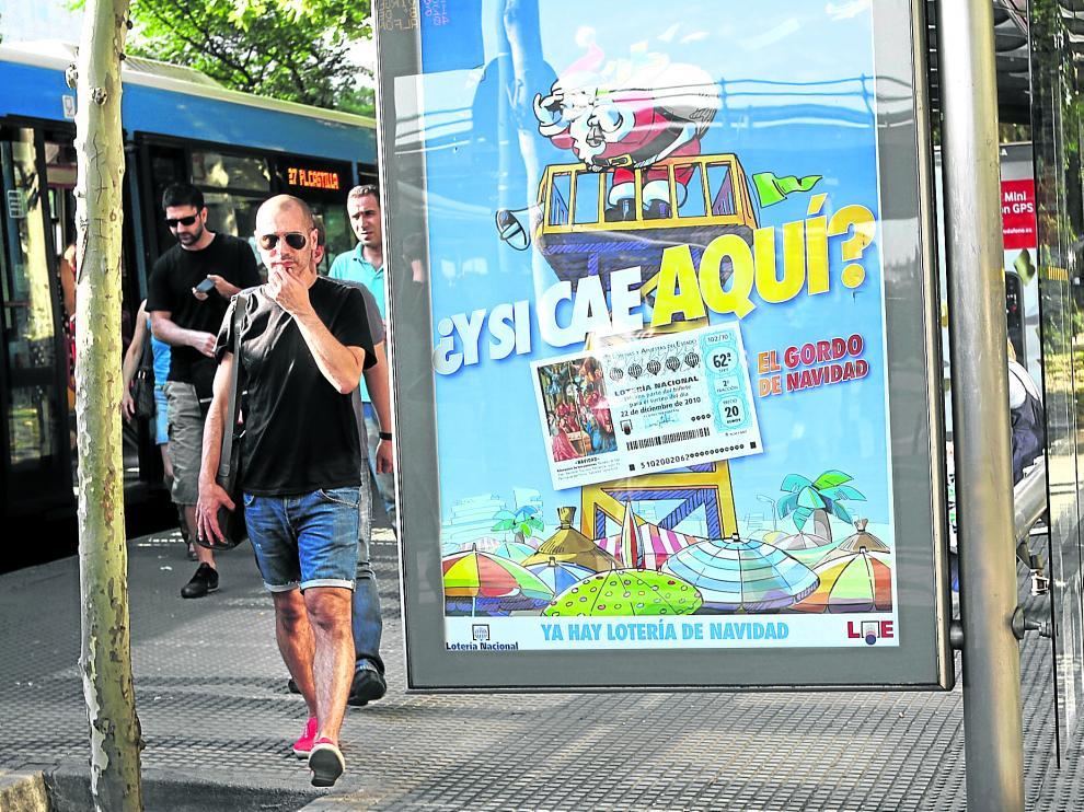 Cartel que anuncia el sorteo de Lotería de Navidad expuesto en una marquesina de autobús en pleno verano.